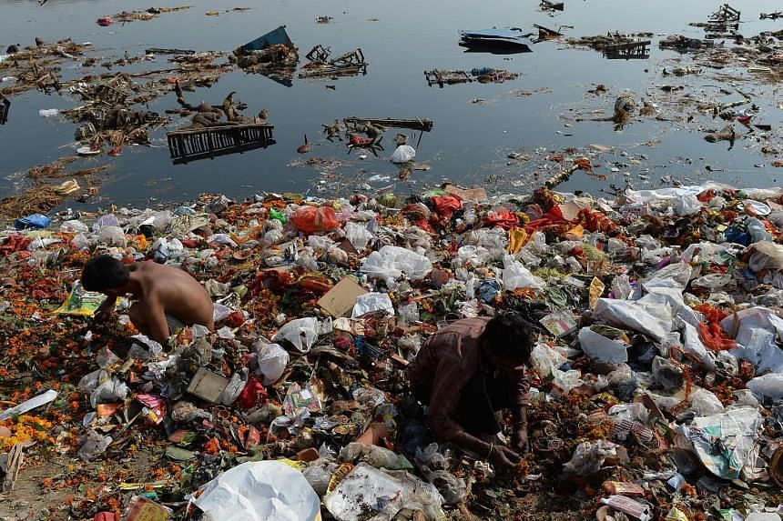 This file photo taken on Oct 12 last year shows scavengers looking for coins and other items among the religious offerings piled up in the badly polluted Yamuna River in New Delhi.