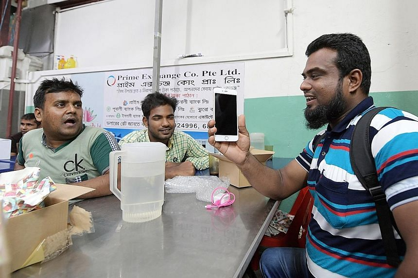 Mr Madbaryousuf with his iPhone 6 Plus at the phone giveaway last night. He was among 50-plus migrant workers who received upgraded phones, thanks to a campaign by Transient Workers Count Too.