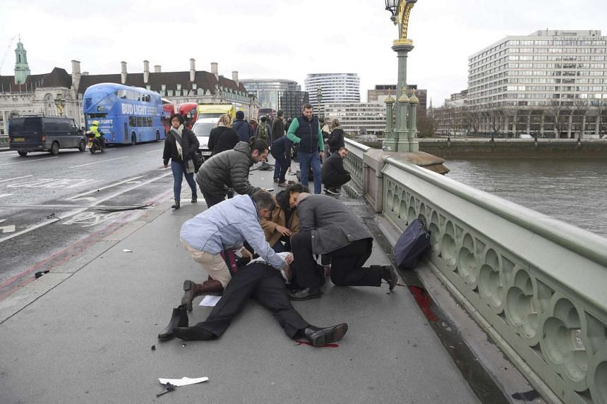 An injured person being attended to after a shooting incident on Westminster Bridge in London, March 22, 2017.