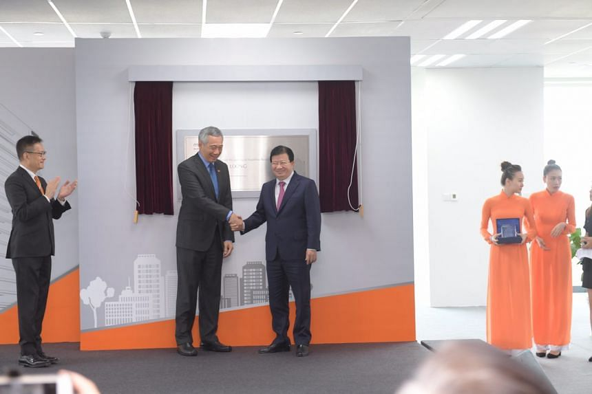 Prime Minister Lee Hsien Loong, Vietnam's Deputy Prime Minister Trinh Dinh Dung and Mapletree Investment chairman Edmund Cheng unveiling the plaque to open Mapletree Business Centre, a new office tower in Ho Chi Minh City.