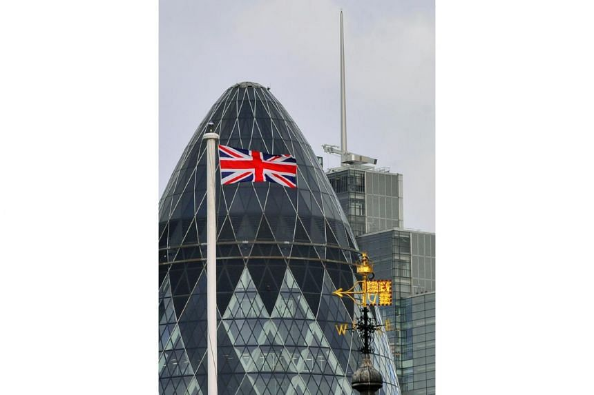 The British Union flag flies in front of 30 St Mary Axe, commonly known as the Gherkin skyscraper, in London.