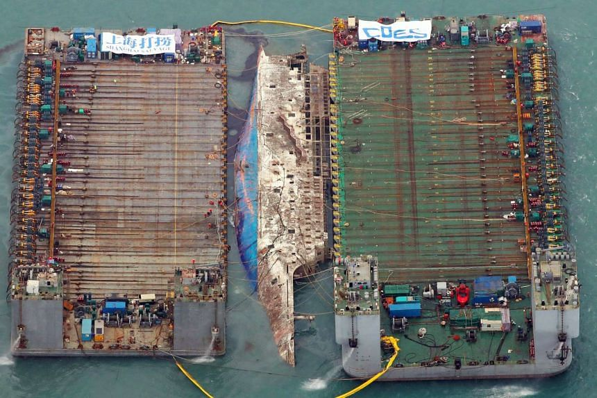 This aerial image shows part of the damaged Sewol ferry between two barges after being raised during a salvage operation at sea off the southwestern island of Jindo on March 23, 2017.