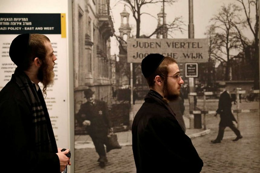 Ultra-Orthodox Jewish visitors stand next to an exhibit during a visit to Yad Vashem's Holocaust History Museum in Jerusalem on Jan 26, 2017.