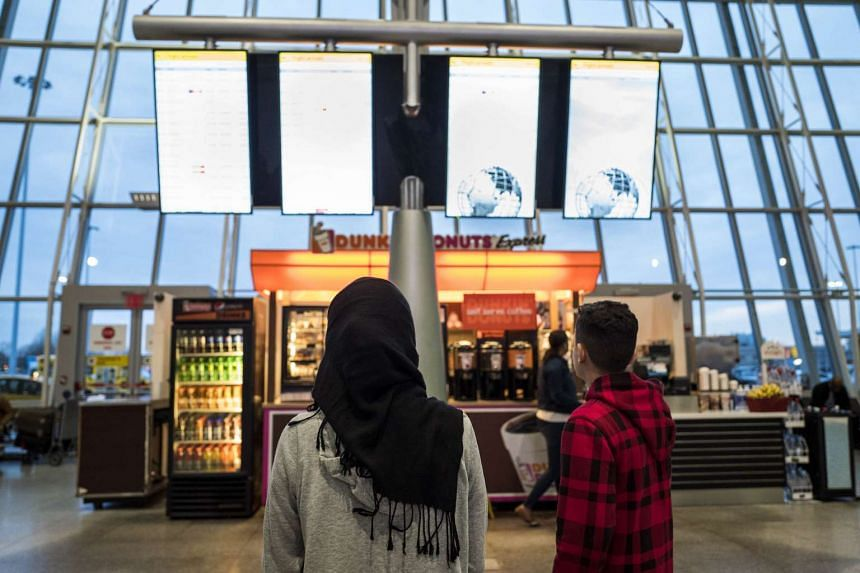 A young woman watches the arrivals board at the international terminal at John F. Kennedy International Airport in New York City on March 6, 2017.