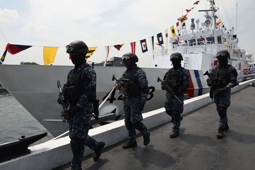 Members of the Philippine coast guard anti-terrorism unit stand next to the newly commissioned coast guard's Multi-Role Response Vessel (MRRV) BRP Malapascua on March 7, 2017.