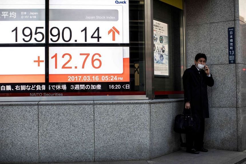 A man talking on his mobile phone next to an electric quotation board flashing the Nikkei key index of the Tokyo Stock Exchange (TSE) in Tokyo.