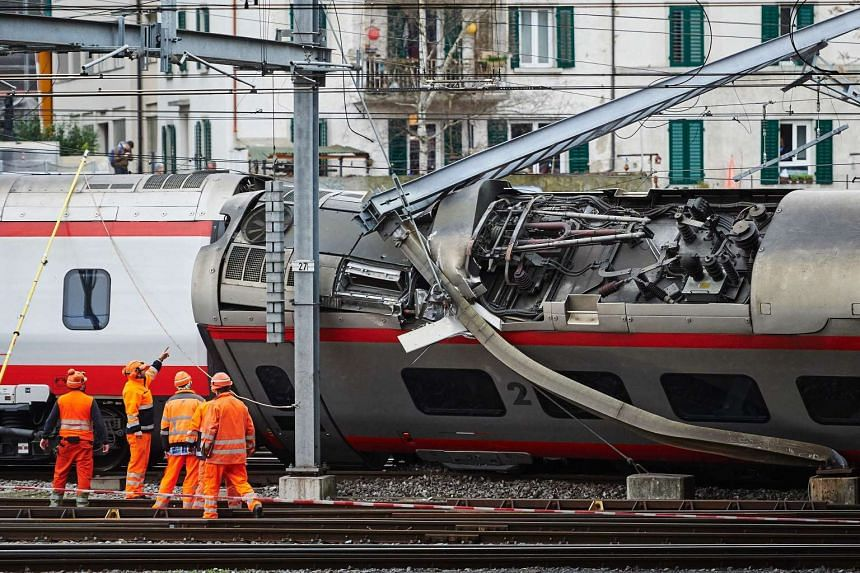 Police officers and workers inspect the site of a train crash at the train station of Lucerne where a Eurocity train of Trenitalia derailed on March 22, 2017 in Lucerne.