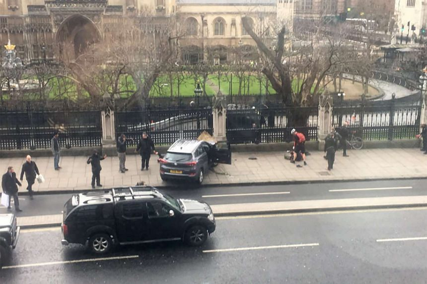 A video grab obtained from the Twitter account of James West, shows a car stopped on the sidewalk in front of the Palace of Westminster which houses the Houses of Parliament in central London on March 22, 2017 during an incident.