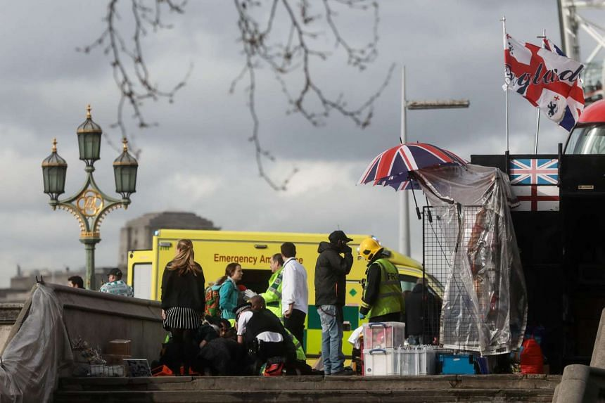 Members of the emergency services tend to an injured individual on Westminster Bridge near the Houses of Parliament in central London on March 22, 2017.