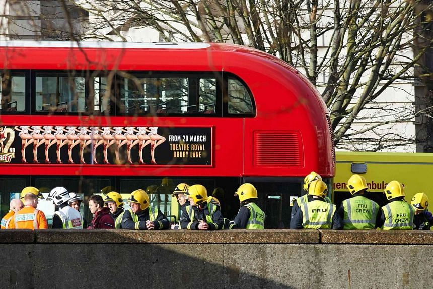 Members of the Ambulance and Fire Brigade emergency services stand alongside a stationary London bus as they work on Westminster Bridge.