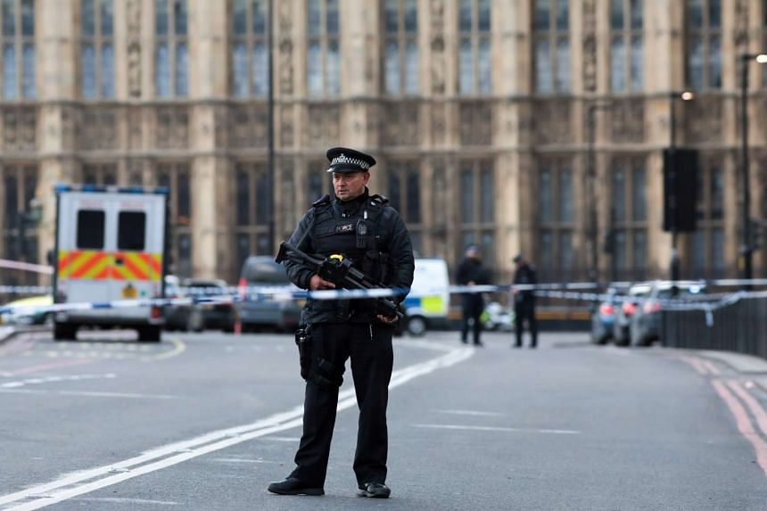 An armed British police officer stands at a cordon near Westminster Bridge and the Houses of Parliament in central London.