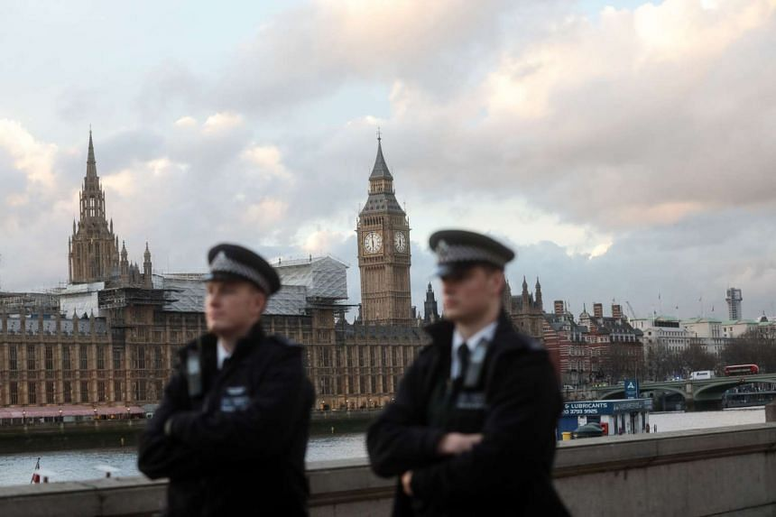 British police officers stand on patrol in view of the Houses of Parliament in central London.