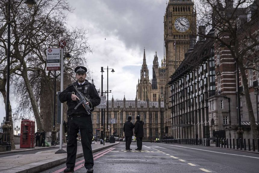 Police officers secure the area near the houses of Parliament in London on March 22, 2017.
