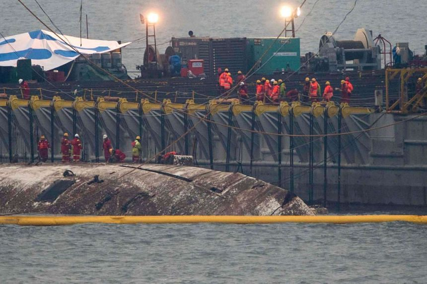 Workers check the surface of the damaged Sewol ferry between two barges during a salvage operation to bring the sunken ship back to surface, off the southwestern island of Jindo on March 23, 2017.