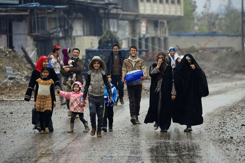 Displaced Iraqis react after reaching safe areas, as Iraqi forces battle with ISIS militants in Mosul, March 23, 2017.