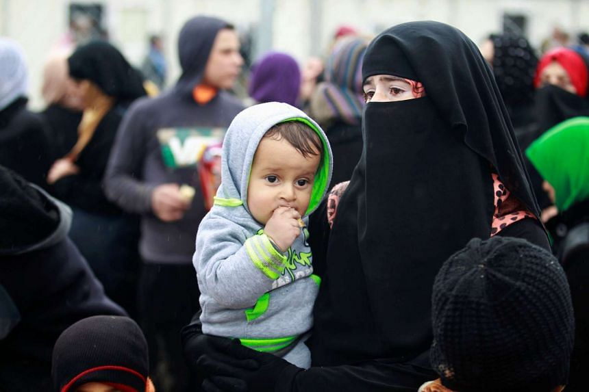 A displaced Iraqi woman carries her child at Hammam al-Alil camp, as Iraqi forces battle ISIS in Mosul, March 23, 2017.