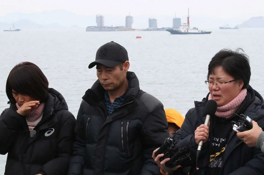 Relatives of the missing from the Sewol ferry disaster talk to the media as they watch a part of damaged Sewol ferry (top far) be raised between two barges during a salvage operation at sea off the southwestern island of Jindo on March 23, 2017.