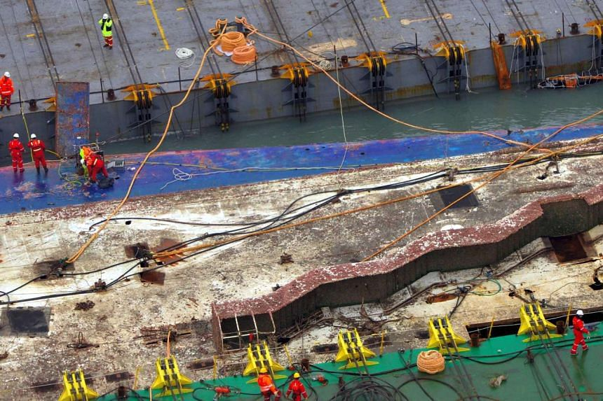 Workers checking on the surface of the damaged Sewol ferry between two barges during a salvage operation to bring the sunken ship back to surface, at sea off the southwestern island of Jindo.