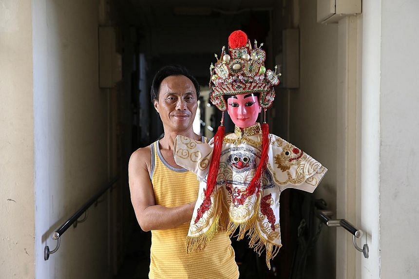 Mr Peter Chew, who leads Hainanese puppet troupe San Chun Long, with a puppet of Wu Song, an ancient Chinese character in novels. Mr Chew's troupe, which has been active since the 1920s, is one of only two such groups left in Singapore.