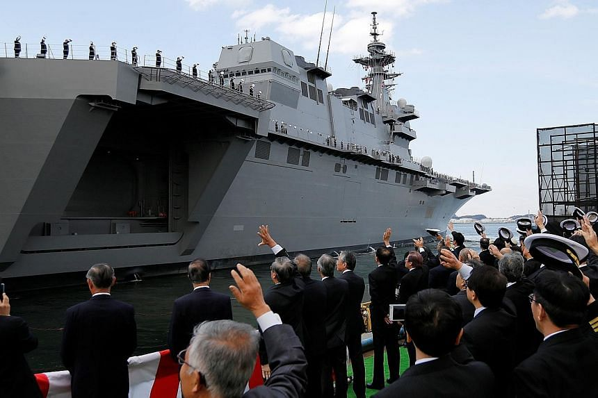 Japanese defence ministry officials seeing off the Kaga, the country's second Izumo-class helicopter carrier, after a handover ceremony at the Japan Marine United shipyard in Yokohama yesterday.
