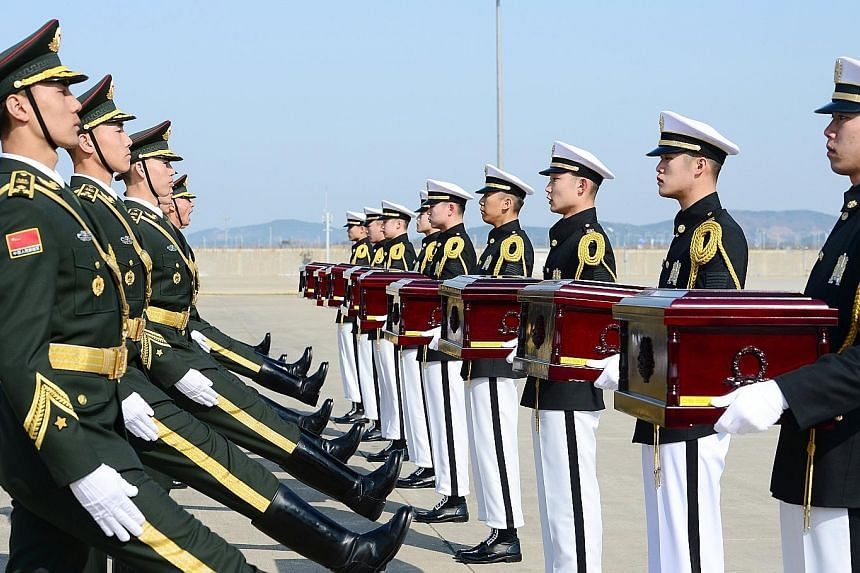 Chinese honour guards receiving boxes which contained the remains of Chinese soldiers killed in the Korean War from their South Korean counterparts during a ceremony at Incheon airport yesterday. South Korea's defence ministry said it went ahead with