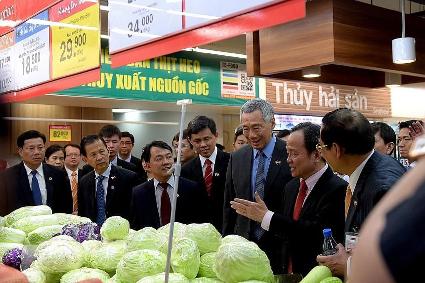 Prime Minister Lee Hsien Loong visiting SC VivoCity shopping mall in Ho Chi Minh City's Saigon South Place Complex yesterday. The complex, developed by Mapletree Investments, includes a new 17-storey office tower which was officially opened yesterday
