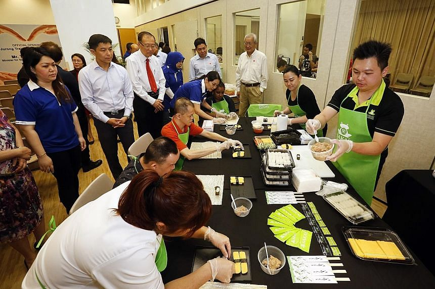 Minister Tan Chuan-Jin and Minds president Jeffrey Tan (with red tie) look on as clients with intellectual disabilities learn sushi-making. Sakae Sushi has committed to training users of the Minds centre.