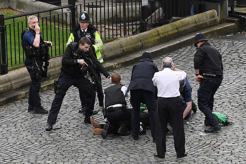 Police officers restraining an injured man, believed to be the attacker, outside the Palace of Westminster in London yesterday. The man allegedly ran into the compound with a knife and was confronted by police officers. He then reportedly stabbed one