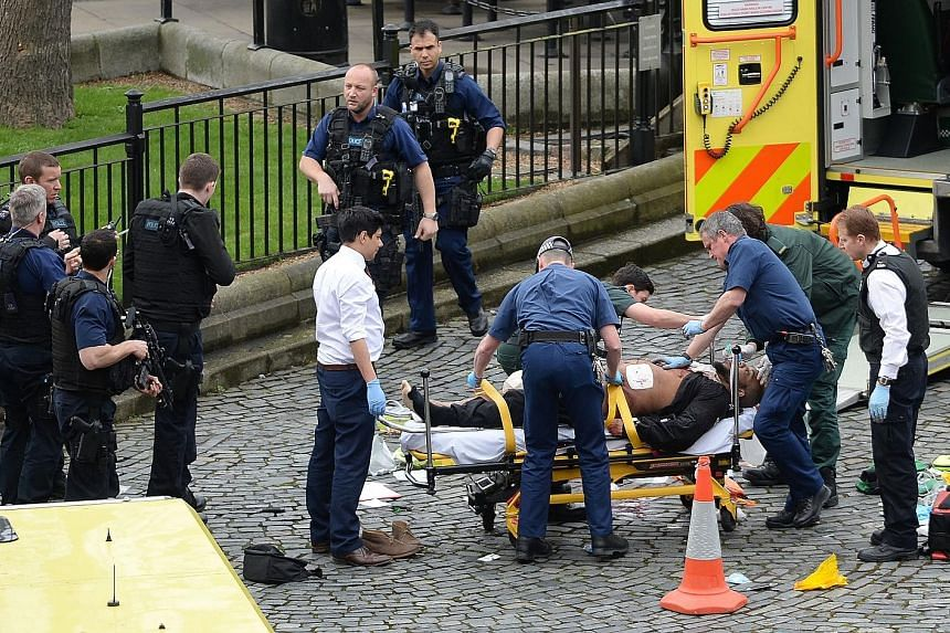 Emergency workers attending to the alleged assailant, who was shot by police after he reportedly made his way into the Parliament grounds and attacked an officer. Members of the public being taken to safety near Westminster Bridge, where eyewitnesses