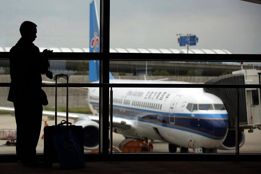 A passenger is silhouetted against a window as a China Southern Airlines Co. aircraft stands at Shanghai Pudong International Airport in Shanghai.