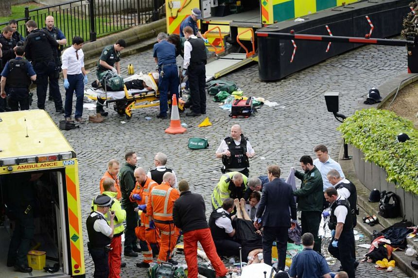 Conservative MP Tobias Ellwood (bottom right) stands amongst the emergency services at the scene outside the Palace of Westminster, London on March 23, 2017.