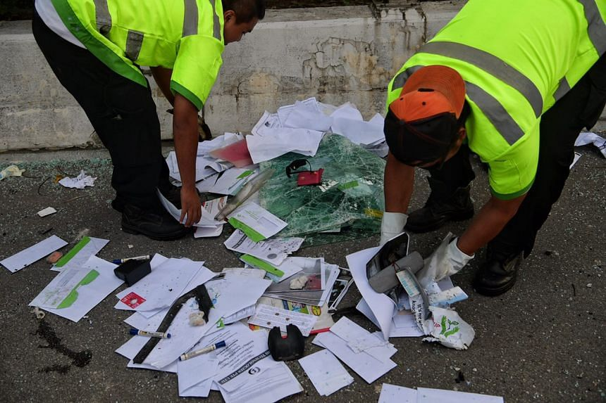EMAS Vehicle Recovery employees clearing up items that were strewn onto the road from a lorry which was involved in an accident with a trailer along the AYE, near the Jurong Town Hall exit, on March 23, 2017.