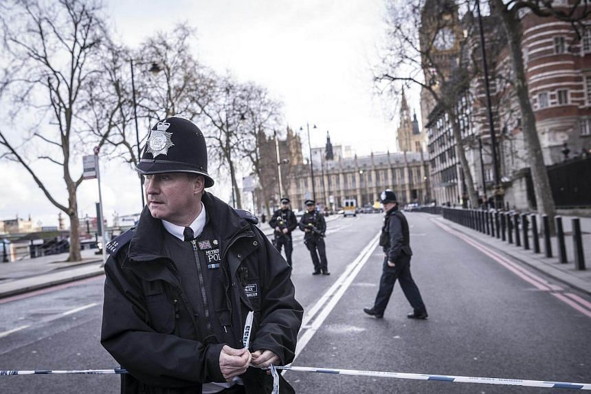 Police officers secure the area near the houses of Parliament in London.