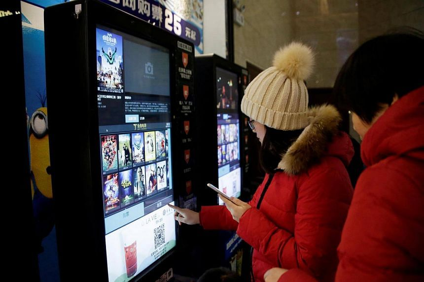 People print movie tickets from a machine at a cinema in Tianjin, China on Jan 13, 2017.