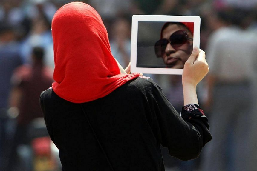 An Egyptian woman using her tablet to video protesters in Cairo's landmark Tahrir Square on June 3, 2012.