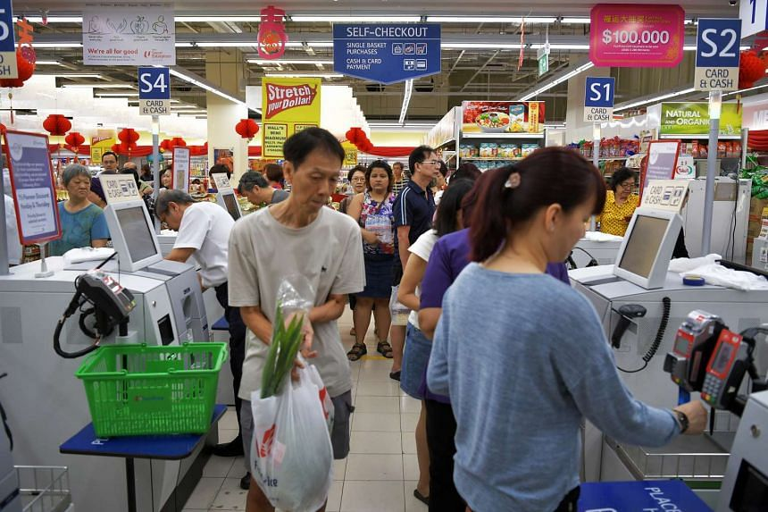 Shoppers at the self-checkout counters at NTUC Fairprice outlet at Toa Payoh HDB Hub during the Chinese New Year.