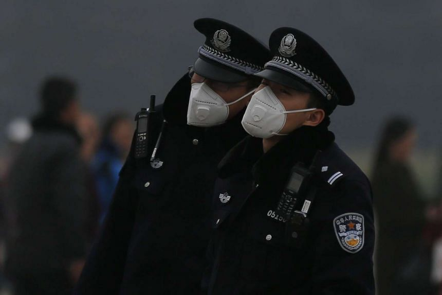 Two policemen stand guard at Tiananmen Square during a hazy day in Beijing, China, on March 20, 2017.