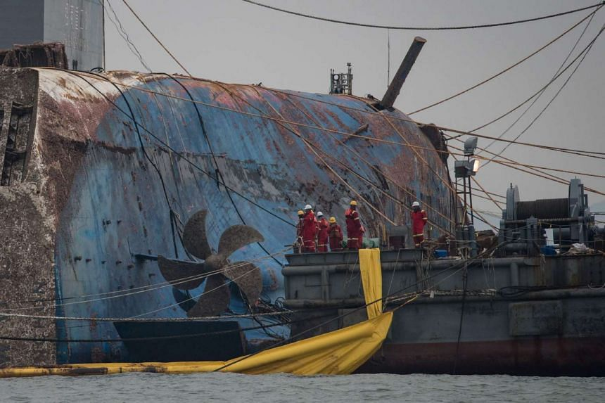 Workers stand before a propellor of the wreck of the Sewol ferry during its the salvage operation off the coast of South Korea's southern island of Jindo on March 24, 2017.