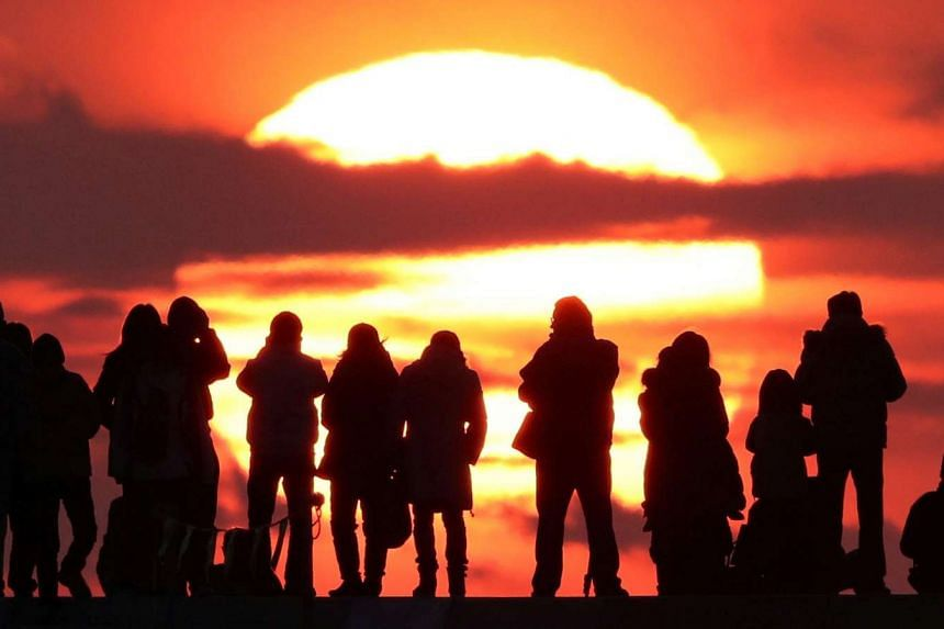 People watch the first sunrise of 2017 in Natori, Japan.