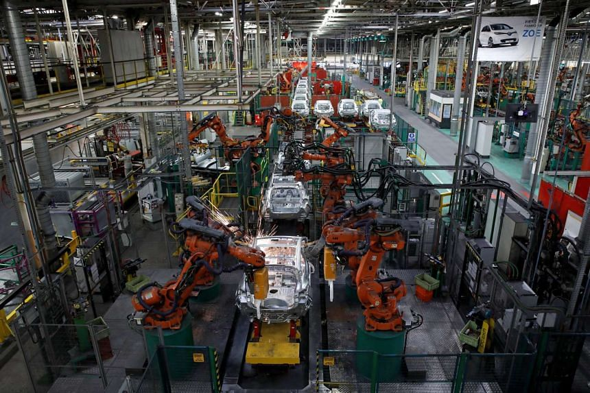 Robots assemble Renault and Nissan vehicles on a production line at the Renault car factory in Flins, near Paris.