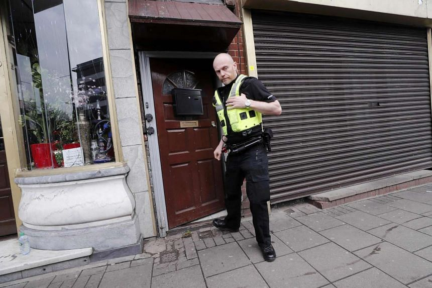 A police officer enters a property in Birmingham that was raided after the attack in Westminster.