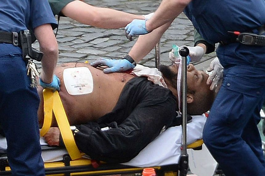 The man identified in British media reports as Khalid Masood, being treated after the attack by the emergency services.