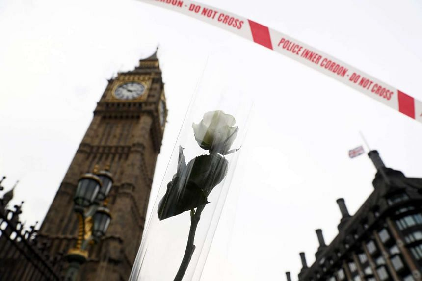 A floral tribute is seen next to police tape by the Houses of Parliament in Westminster the day after an attack, in London, March 23, 2017.