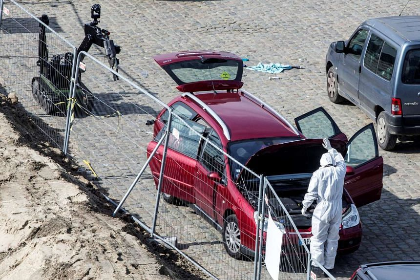 A forensics expert stands next to a car which had entered the main pedestrian shopping street in the city at high speed, in Antwerp, Belgium, on March 23, 2017.