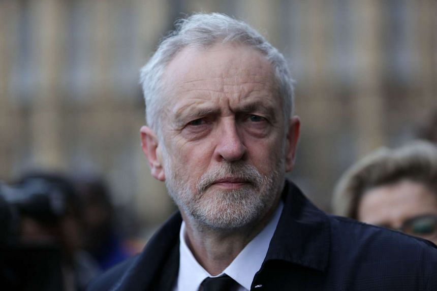 British Opposition Labour Party leader Jeremy Corbyn walks along Westminster Bridge by the Houses of Parliament in central London on March 23, 2017.
