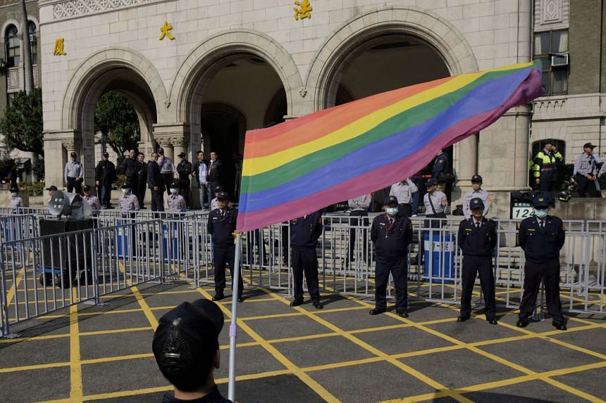 A supporter of same-sex marriage waves a flag outside the Judicial Yuan in Taipei on March 24, 2017.