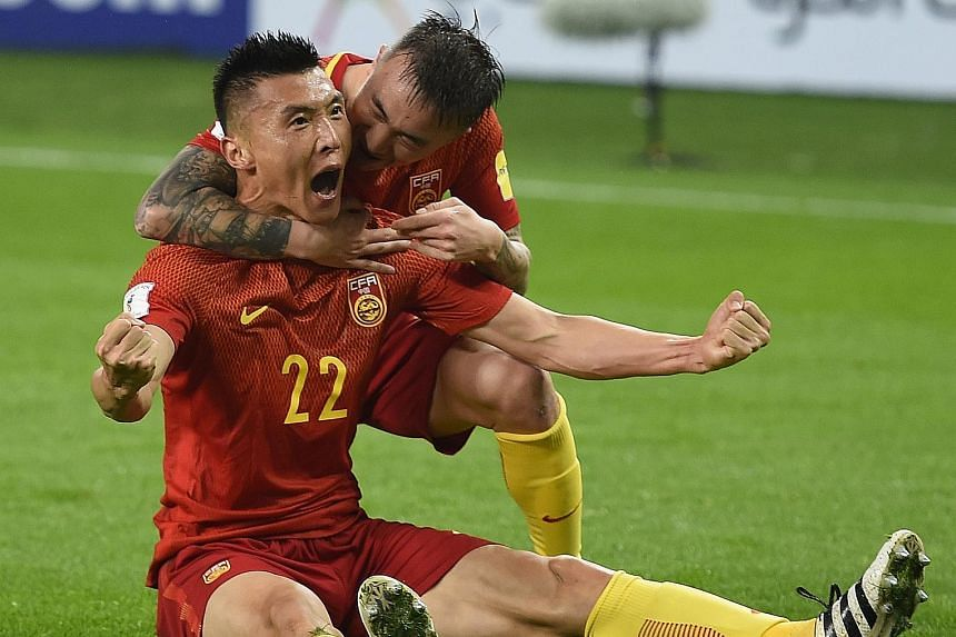 China's Yu Dabao celebrating his 34th-minute goal against South Korea with Wang Yongpo. The goal was the sole difference between both sides and a win against Syria in their next game could put China back in contention for a play-off spot.