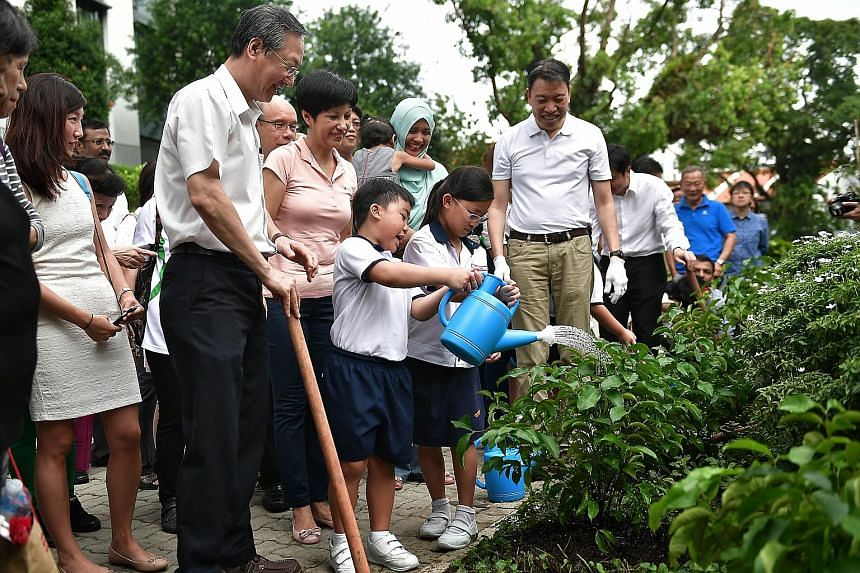 Cantonment Primary School pupils watering some of the shrubs planted in Tanjong Pagar GRC yesterday to mark two years since Mr Lee's death. With them are (from left) Radin Mas MP Sam Tan (foreground), who is also Minister of State in the PMO and for