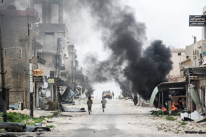 """A plume of smoke from a burning tyre rising amid the destruction in the Syrian town of Tayyibat al-Imam in Aleppo on Wednesday. Mr Tillerson did not make clear where the """"interim zones"""" were to be set up, or how they would work, but creating such saf"""