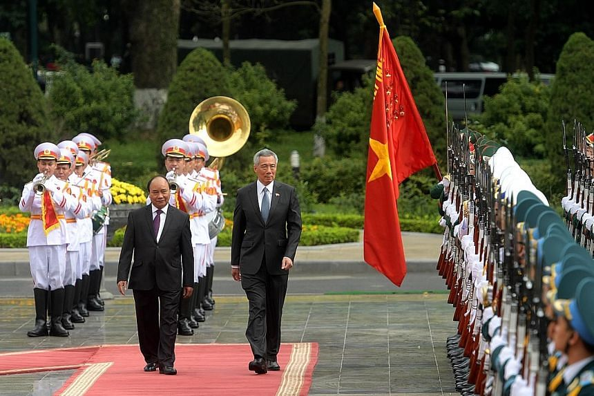 PM Lee being welcomed by Vietnamese PM Phuc at a ceremony in Hanoi's Presidential Palace yesterday.